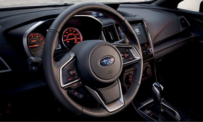 Exclusive red stitching on the dash and steering wheel plus a performance-inspired gauge cluster reveal the aggressive side of the Impreza 2.0i Sport.