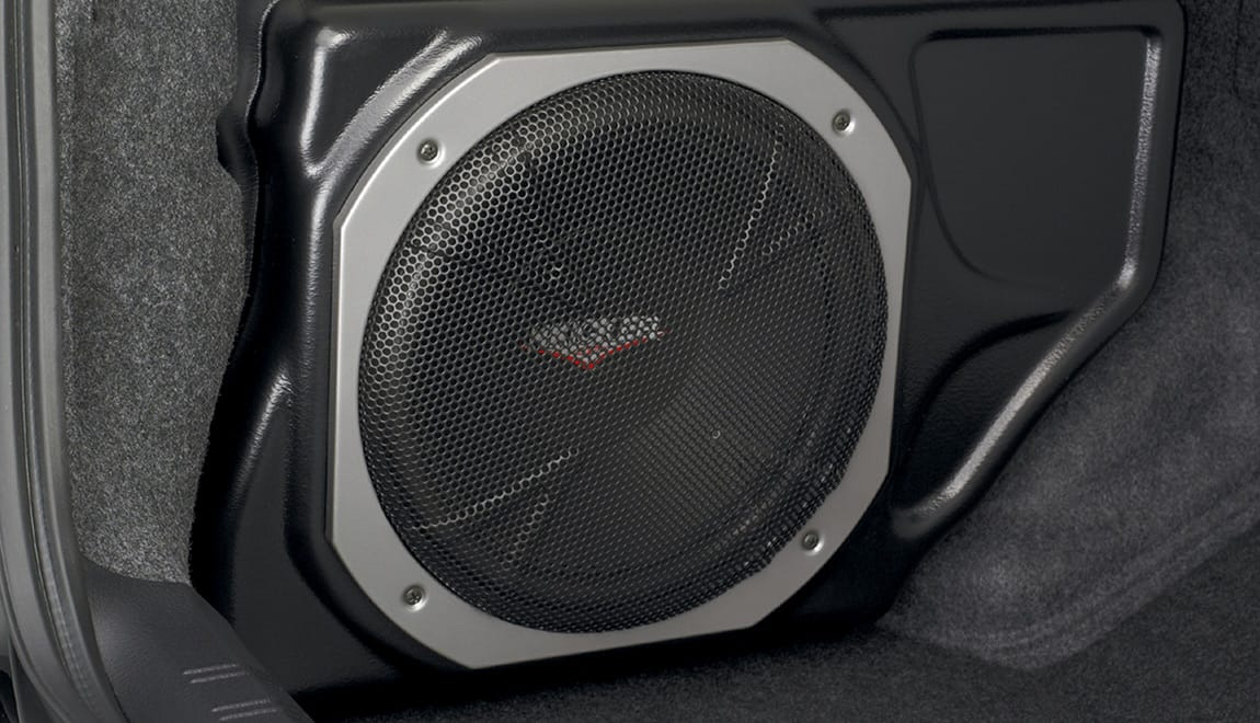 Provides powerful, deep bass and also assists in clean sound reproduction from all vehicle speakers. This is achieved by its integrated 100W amplifier and a passive crossover network. The self-contained unit mounts in the trunk. Manufactured for Subaru of America by Kicker<sup>®</sup>.